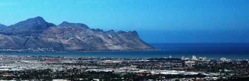 Panoramic of Strand, South Africa. Panoramic, overhead view of Table Bay and the suburb of Strand, near Cape Town, South Africa, with mountains in the background stock photo