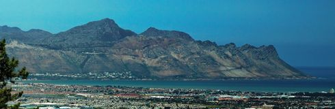 Panoramic of Strand, South Africa. Panoramic, overhead view of Table Bay and the suburb of Strand, near Cape Town, South Africa, with mountains in the background stock image