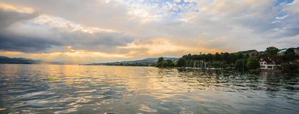 Panoramic summer view of boat cruise excursion landscape on Zurichsee with beautiful sunset shining light through clouds reflected. The golden light on the Royalty Free Stock Photography