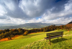 Panoramic sunny autumn alpine view with bench. Sunny autumn alpine panorama with beautiful view and with a bench for rest in the foreground Stock Photography