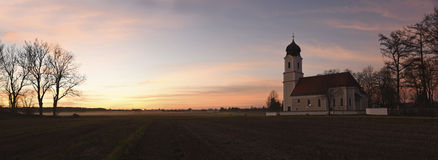 Panoramic sunset scenery with fog over the fields and chapel Stock Image