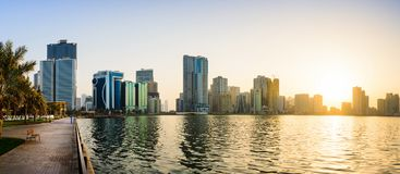 Panoramic view of Sharjah waterfront in UAE at sunset. Panoramic sunset view of Sharjah waterfront cityscape in UAE Royalty Free Stock Photography
