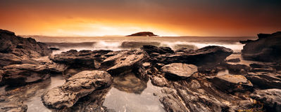 Panoramic Surf. Surf rolling in over some jagged rocks Stock Image