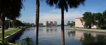 Panoramic tropical inlet. A tropical panoramic view of an inlet on the ocean with the palms on the front and city buildings in the background stock photo