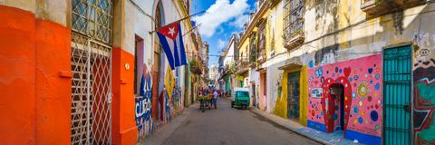Urban scene with a cuban flag on a colorful street in Havana. Panoramic urban scene with a cuban flag on a colorful street in Old Havana royalty free stock images