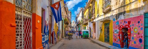 Urban scene with a cuban flag on a colorful street in Havana. Panoramic urban scene with a cuban flag on a colorful street in Old Havana royalty free stock photography