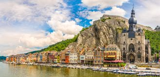 Panoramic vew at the embankment of Meuse river with houses and church of Our Lady Assumption in Dinant - Belgium Stock Photography