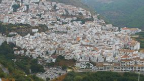 Panoramic view from above of a white village in the mountains of Spain. Spanish white city of Andalusia surrounded by mountains and trees stock footage