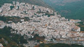 Panoramic view from above of a white village in the mountains of Spain. Spanish white city of Andalusia surrounded by mountains and trees stock video footage