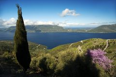 Kefalonia Island, Greece. A panoramic view across the Ionian Sea from the Greek island of Kefalonia to the neighboring island of Ithaca with a tall Stock Image