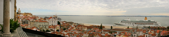 Panoramic view of the Alfama neighbourhood and Tagus river in Lisbon, with red rooftops and a cruise ship Stock Images