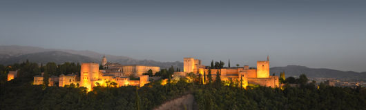 Panoramic view of the Alhambra at dusk. The Alhambra, in Granada, Spain at twilight. Evening panorama Royalty Free Stock Photos