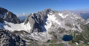 Panoramic view of an alpine ridge with mountain lake Stock Images