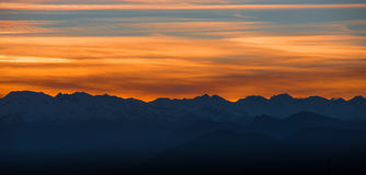 Panoramic view of alpine snowcapped mountain peaks at sunset. Royalty Free Stock Photography