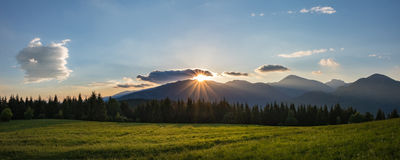 Panoramic view of amazing mountains sunset. With sun, blue sky, clouds, forest and meadow - Little Fatra hills National Park, Slovakia, Europe Royalty Free Stock Photo