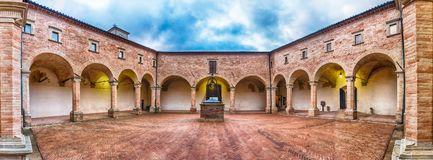 Ancient cloister of the Basilica of Saint Ubaldo, Gubbio, Italy. Panoramic view of the ancient cloister inside the Basilica of Saint Ubaldo, a roman catholic Royalty Free Stock Photos