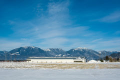 Panoramic view on animal farm on winter sunny day on blue sky background. Modern industrial agriculture building in Fraser Valley on mountaing view background Royalty Free Stock Image