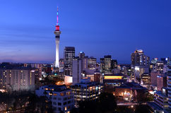 Panoramic view of Auckland Sky tower skyline in colors at dusk. AUCKLAND - AUG 03 2015:Panoramic view of Auckland Sky tower skyline in colors at dusk.Auckland is Stock Images