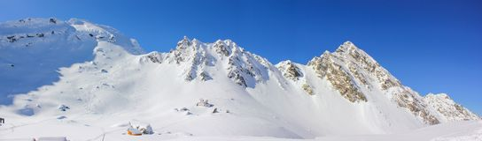Panoramic view of Balea Lake with cabin and Fagaras Mountains. Alpine winter landscape with cabin at Balea Lake and Fagaras Mountains covered with snow in Sibiu Stock Photo