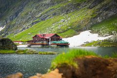 Panoramic view of Balea Lake and cabin. With Fagaras Mountains background Stock Photo