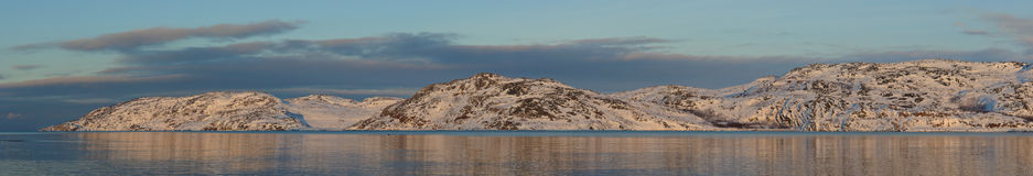 Panoramic view of the Barents Sea coastline in spring sunset. Royalty Free Stock Photography