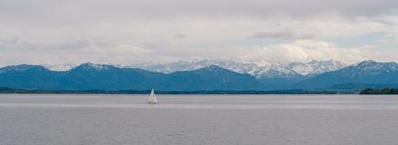 Panoramic view of German lake `Starnberger See` with beautiful alp mountains. Panoramic view of Bavarian lake with lonely sailing ship and alp mountains in the royalty free stock photos