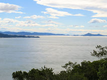 Panoramic view of the bay and sky with clouds. In summer day, with forest in the foreground Stock Photos