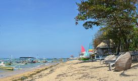 Beach Chairs & Sailing Boats on Sanur Beach, Bali Indonesia Royalty Free Stock Image