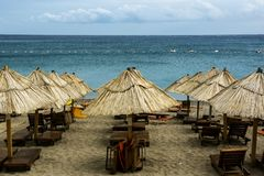 Panoramic view of the beach with ranks of chaise lounges and umbrellas from straw. Panoramic view of beach with ranks of chaise lounges and umbrellas from straw stock image