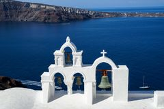 Panoramic view of beautiful blue Aegean sea, sailing ship and caldera from Oia village with white church roof foreground. And blue sky background, Santorini Royalty Free Stock Image