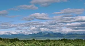Panoramic view of beautiful clouds over a green hill valley stock images
