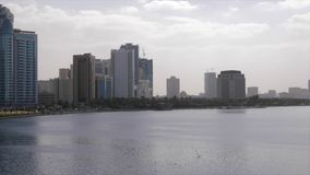 Panoramic view of beautiful lake surrounded by city buildings. Panoramic view of beautiful lake surrounded by tall modern city buildings against cloudy sky on stock footage