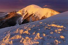 Panoramic view of beautiful winter wonderland mountain scenery in evening light at sunset. Mountains above the clouds. stock photo