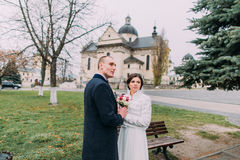 Panoramic view of beaytiful newlywed couple holding hands and looking afar in park near old baroque church Royalty Free Stock Image