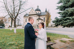 Panoramic view of beaytiful newlywed couple sensually holding hands in park near old baroque church Royalty Free Stock Photos