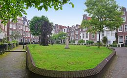 Panoramic View of Begijnhof with large green area with trees in the middle at capital city Amsterdam
