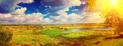 Panoramic view on big meadow with small flood sky with sun insta Stock Images