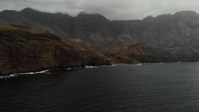 Panoramic view of the big mountains off the coast of the Atlantic Ocean on a cloudy day. Bird`s eye view. Agaete, Gran. Canaria 2k stock footage