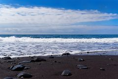 Panoramic view on a black sand beach against blue sky. Praia Formosa beach in Funchal on Portuguese island of Madeira royalty free stock photos