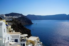 Panoramic view of blue Aegean sea, sailing ships and ocean water reflection from Oia village with white buildings cityscape. Along island mountain and blue sky Stock Photos