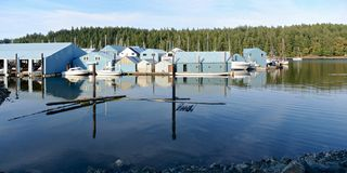 Blue boat houses reflected in the water on the background of coniferous fores royalty free stock photography