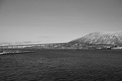 Panoramic view from boat on Tromso landscape with snowy mountains and city harbor in black and white, Norway Stock Images