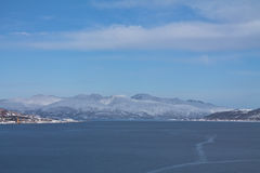 Panoramic view from boat on Tromso landscape with snowy mountains and city harbor in sunny blue sky, Norway Stock Photo