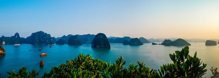 Panoramic view of boats floating in the tranquil waters of Halong Bay Vietnam at sunset. Panoramic view from hilltop of boats floating in the tranquil waters of stock photo