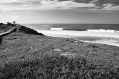 Panoramic view on breaking waves of atlantic ocean on amado beach with people observing surfers Royalty Free Stock Photo