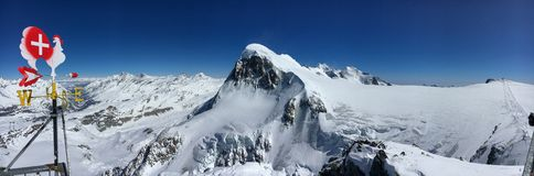 Panoramic view of Breithorn mountain and Matter Valley with wind vane weathercock in the foreground. Beautiful panoramic view of Breithorn mountain and Matter stock image