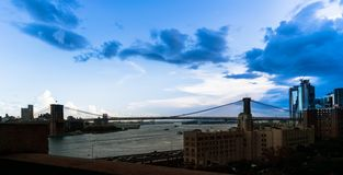 Panoramic view of the Brooklyn Bridge spanning the East River, beneath a vast blue early-evening sky in Downtown stock images