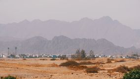 Panoramic view of buildings and houses in the desert mountains in the background in Egypt. Sharm el Sheikh. Mirage, hot weather, evaporation. Hot desert, heat stock video