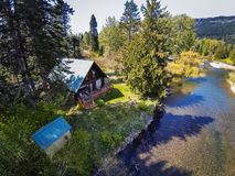 Panoramic view of cabin style home on a river bank. Panoramic view of cabin style home on river bank with lots of greenery Stock Photography