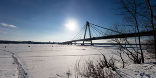 Panoramic view of cable-stayed pipeline in Chrepovetz, Russia in winter sunny day. Group  skiers and fishermen at the. Panoramic view of cable-stayed pipeline in Stock Images